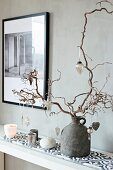 Baubles hung from contorted hazel branch and arrangement of candles on patterned tiles against grey wall