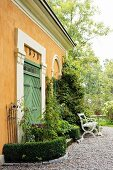 Bench and table on gravel terrace outside yellow limewashed country house with green wooden door