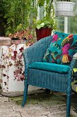 Blue-painted wicker chair and cushion with bird motif in greenhouse