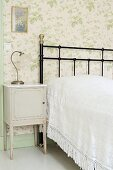 Rustic bedside table, black wrought iron bed and floral wallpaper