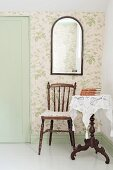 Chair with turned legs, white lace cloth on dark wood side table and mirror on wallpapered wall in corner