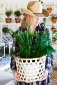 Woman wearing straw hat holding foliage plant in decorative pot