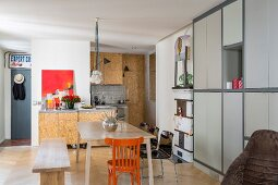Simple wooden bench, orange chair and fitted cupboards with pale grey fronts in dining area of modern kitchen