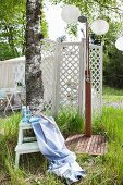 Rainfall outdoor shower, bathroom utensils on white stepladder and screen in summery garden