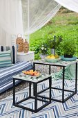 Two-piece side table set with patterned tiled tops on rug in furnished garden pavilion