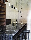 Black granite counter, empty wooden shelves and concrete wall