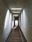 Corridor with sloping floor and concrete walls and ceiling