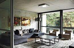 Modern living room with concrete ceiling and walls and glass wall