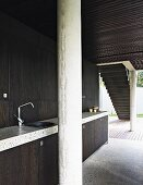 Minimalist kitchen with dark wooden fronts, concrete column and glass wall