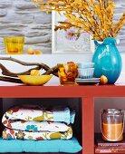 Äste, Zweige und Accessoires als herbstliche Deko auf orangefarbenem Lackregal