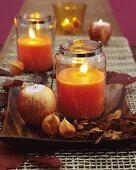 Windlichter gefüllt mit orangefarbenem Wachs herbstlich dekoriert mit Blättern und Zweigen