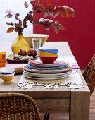 Farbenfrohes Geschirr und handgefertigte Tischsets aus Holzfunier auf rustikalem Holztisch