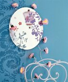 Round mirror with butterfly motifs and floral fairy lights on blue wall