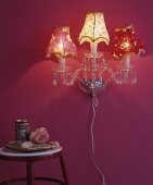 Vintage-style crystal wall lamp with fabric lampshades on pink wall