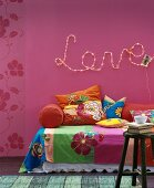 Floral throws and cushions on sofa below motto 'Love' written in fairy lights on deep pink wall