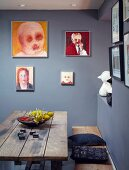 Rustic wooden bench and table below portraits on grey-blue walls in corner