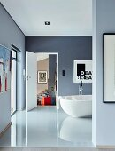 Glossy tiled floor and free-standing white bathtub in blue-grey bathroom