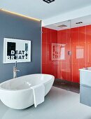 Free-standing white bathtub on tiled floor next to glazed shower area with orange-red wall tiles