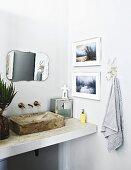 Waschtisch mit Waschbecken aus Beton, an Wand Vintage Spiegel und gerahmte Fotos