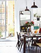 Esstisch mit Protea dekoriert, darüber Pendelleuchten im Industriestil, im Hintergrund offene Terrassentür
