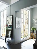 Offener Wohnbereich mit raumhohen Sprossenfenstern, an Wand Standspiegel in einer Loft-Wohnung