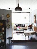 Offener Wohnbereich mit verschiedenen Sitzmöbeln um niedrigen Couchtisch, im Vordergrund Raumteiler