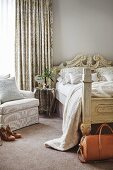 Antique wooden bed with carved headboard, delicate table and armchair in front of elegant curtain