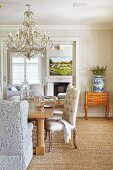 Crystal chandelier above dining table with chunky legs, armchairs and Baroque upholstered dining chairs on sisal rug