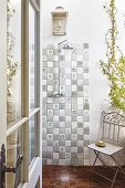 Vintage folding chair next to tiled shower area, climbing plant and candle lantern mounted on wall
