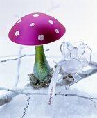 Märchenhafte Weihnachtsdeko mit pinkfarbenem Dekopilz auf Zweig