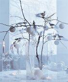 Weisse Weihnachten: Zweige in Glasvase dekoriert mit Baumkugeln, Sternanhängern und silbernen Dekovögeln