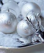 Beschriftete silberne Christbaumkugeln auf dekorativem Silberteller