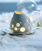 Dekoratives Porzellan-Windlicht auf weisser Felldecke
