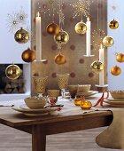 Goldene Baumkugeln, weisse Kerzen und glitzernde Dekosterne aufgehängt über gedecktem Esstisch