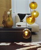 Gold spherical pendant lamps, animal-skin rug, coffee table and modern chaise in living room