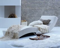 Teapot on tray on fur rug next to chaise longue next to fireplace