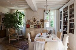 Oval dining table and loose-covered chairs in rustic, country-house dining room