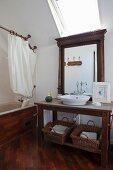 Dark wooden washstand below mirror and skylight next to wood-clad bathtub with shower curtain