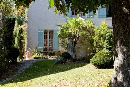 Sunny garden of country house with pale blue shutters