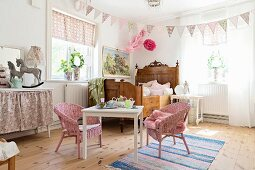 Antique wooden bed and children's table and chairs in girl's bedroom