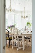 View of set dining table and antique chairs through open door
