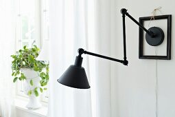 Black anglepoise lamp with black frame around wall-mount
