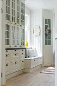 Country-house kitchen with glass-fronted dresser and integrated windowseat