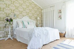Green wallpaper and white furniture in Scandinavian-style bedroom