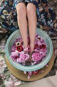 Woman bathing feet in bowl of water and flowers