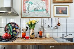 Vase of narcissus and kitchen utensils on worksurface against white-tiled splashback
