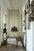 Thonet chair against wall in narrow hallway with terrazzo floor in period apartment