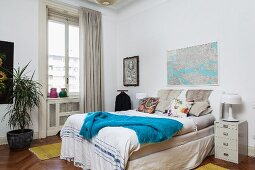 Blue blanket on comfortable box-spring bed in front of window with floor-length curtains in simple bedroom