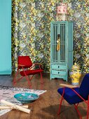 Retro armchairs, Chinese porcelain accessories and turquoise cupboard against patterned wallpaper