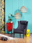 Wicker lampshades above grey armchair, Chinese cabinet and stool in front of turquoise wall
